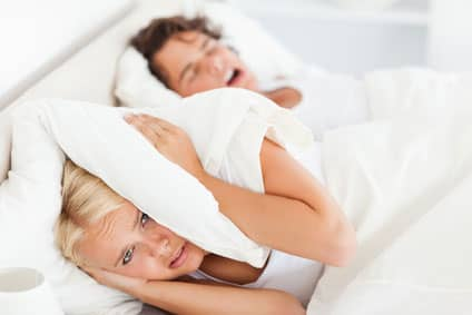 A woman covering her ears with a pillow unable to sleep because of her husband's snoring