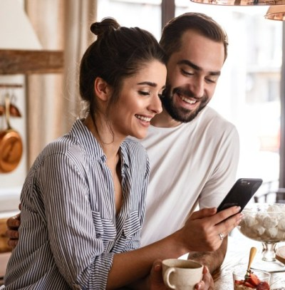 photo of a woman and a man looking at a mobile phone